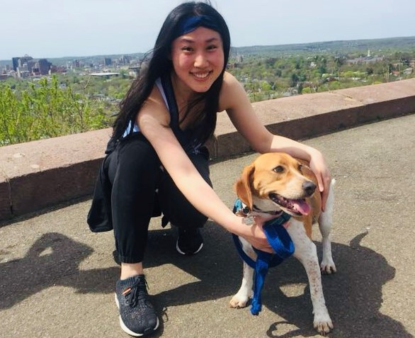 Hooded Horse's game music composer plays with her adorable dog, a white and tan beagle, in a park overlooking a Connecticut forest.